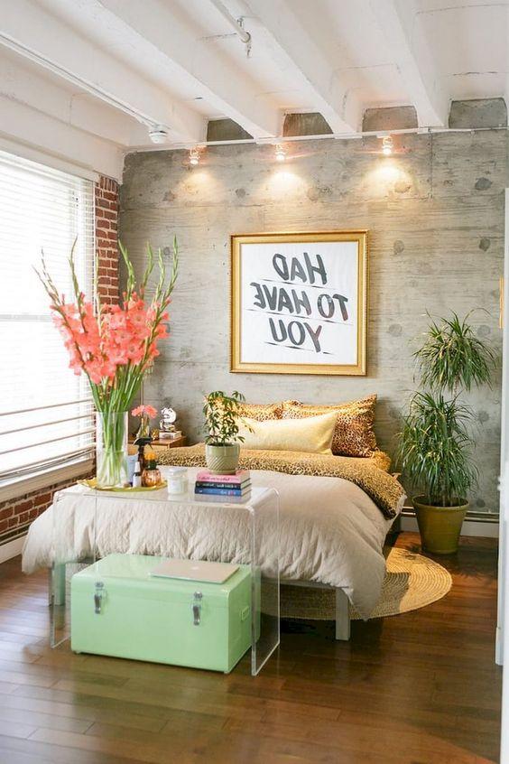 una camera da letto eclettica con una stampa animalier, mattoni, una console acrilica, una cassapanca menta e altri tocchi glam