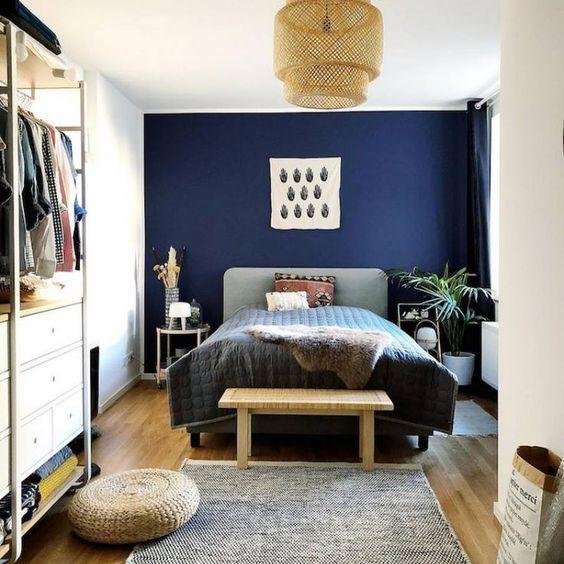 una camera da letto eclettica con un letto imbottito, paralumi in vimini, oggetti di iuta e vimini e un armadio contemporaneo