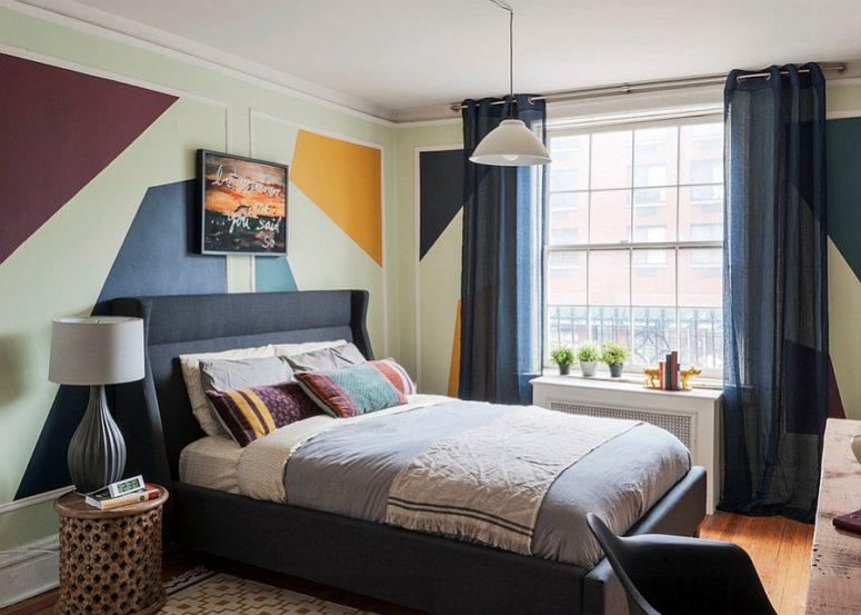 una camera da letto geometrica eclettica con stencil sui wlals, un letto nero imbottito, sgabelli intagliati e comodini