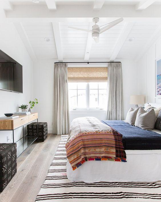una camera da letto eclettica con neutri e vari colori tenui, stampe miste e mobili moderni della metà del secolo