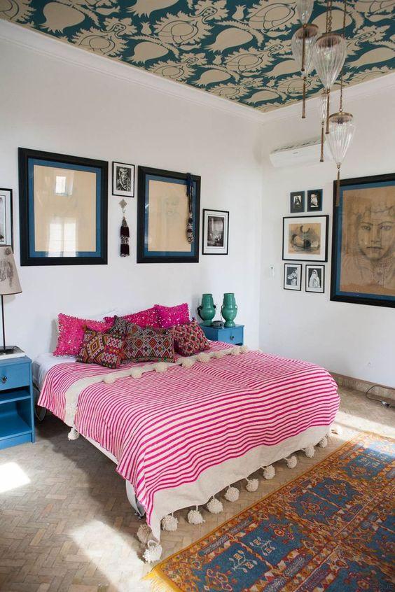 una camera da letto eclettica con un soffitto di carta da parati, un tappeto boho e biancheria da letto con pompon, una varietà di opere d'arte e comodini retrò