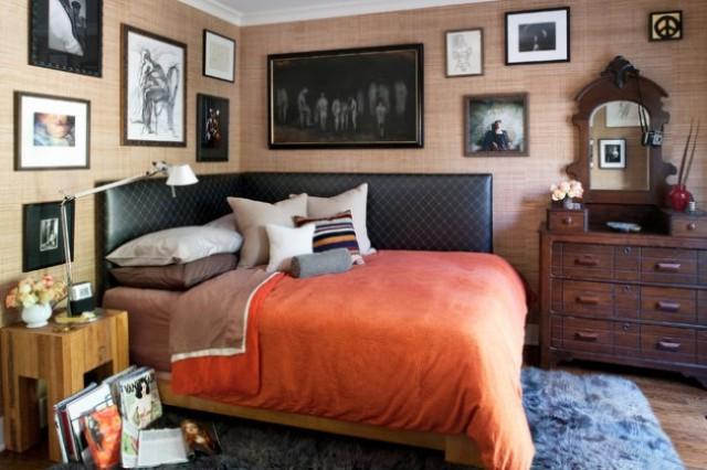 una zona notte eclettica con una credenza e uno specchio macchiati di scuro, un letto in pelle nera, un comodino rustico e un'enorme galleria a parete dappertutto
