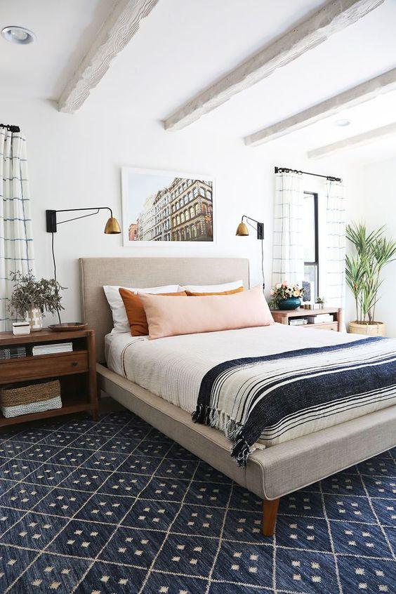 uno spazio per dormire eclettico con un letto imbottito, comodini in legno della metà del secolo, lampade vintage glam e molto altro ancora