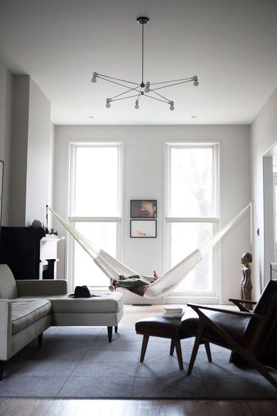 un soggiorno minimal in bianco e nero con mobili neutri e neri, un'amaca, un camino e un lampadario accattivante