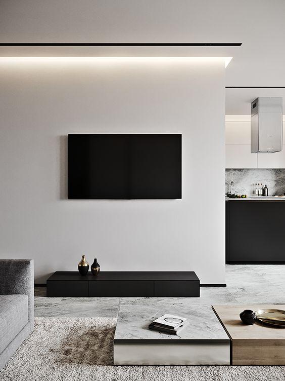 un soggiorno a contrasto in bianco sporco e nero, tavolini laconici, un tappeto materico e luci incorporate