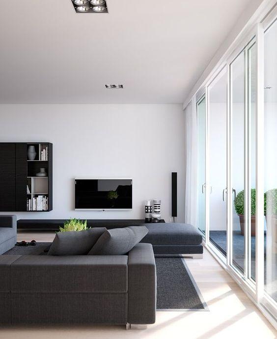 un soggiorno minimal con mobili grigi, una TV, un mobile contenitore a parete e una parete vetrata per molta luce naturale