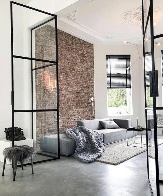 un soggiorno minimal con un muro di mattoni, un divano grigio, un tavolino da caffè nero e sfumature nere