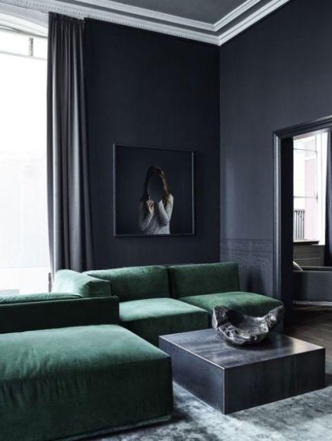 un lunatico soggiorno grigio grafite con tavolini da caffè, un divano componibile color smeraldo e un'opera d'arte