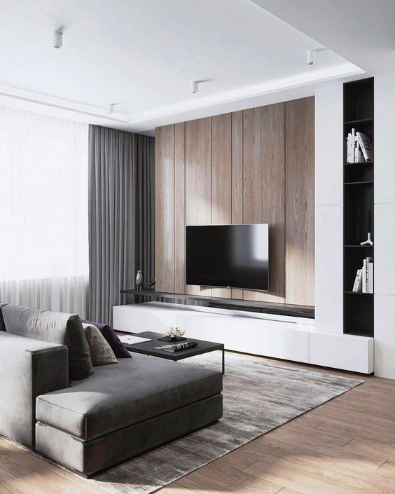 un soggiorno minimal con una parete in legno, tende grigie, un divano e un tappeto più tocchi di nero qua e là
