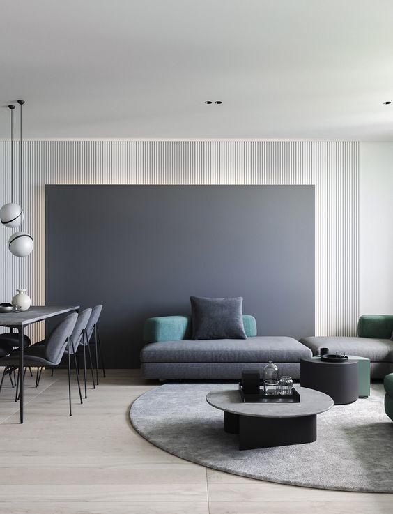 uno spazio abitativo minimalista con una parete a lavagna, tavolini da caffè scuri, un divano componibile grigio e cuscini colorati
