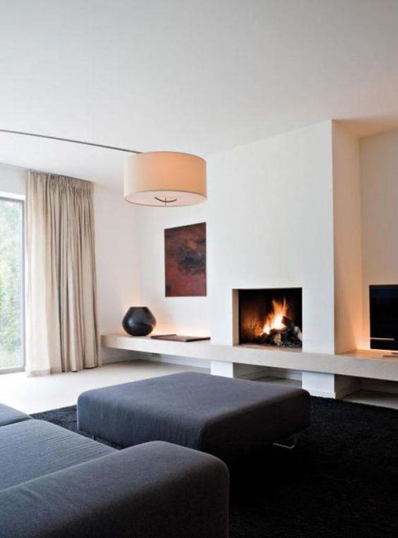 un soggiorno minimal con mobili neri e un tappeto, un camino, un'opera d'arte, una lampada e tende neutre