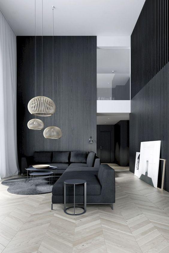 un lunatico soggiorno minimal con pareti nere e un divano componibile, paralumi in rattan e un paio di tavolini