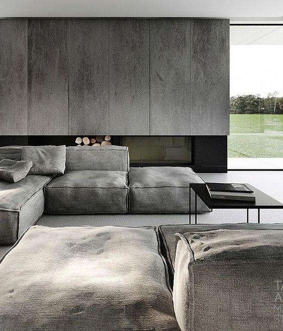 uno spazio abitativo minimalista lunatico con pannelli grigi, un camino incorporato, mobili in tela grigia e tocchi neri