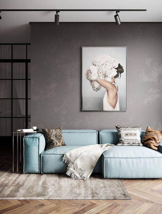 un lunatico soggiorno minimal con un divano aqua, un'opera d'arte, un tappeto e pareti in legno rivestite di chevron