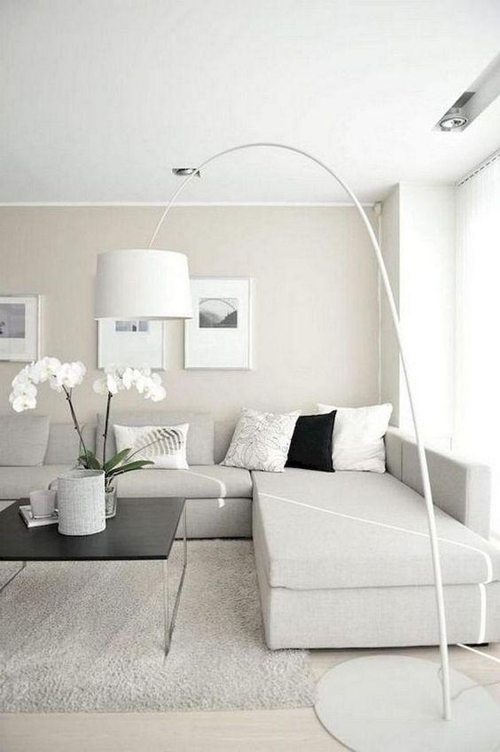 un soggiorno minimalista neutro con un divano componibile bianco sporco, una lampada da terra, opere d'arte e fiori in vaso