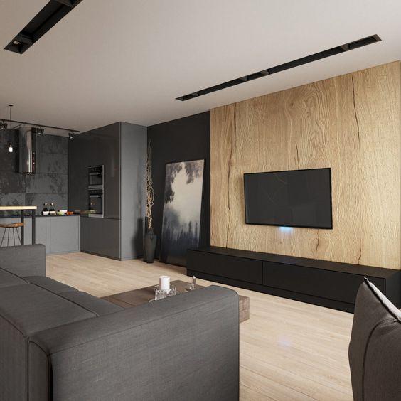 un lunatico soggiorno minimalista con una parete in legno, un divano grigio, tocchi scuri e un'opera d'arte più una TV sul muro