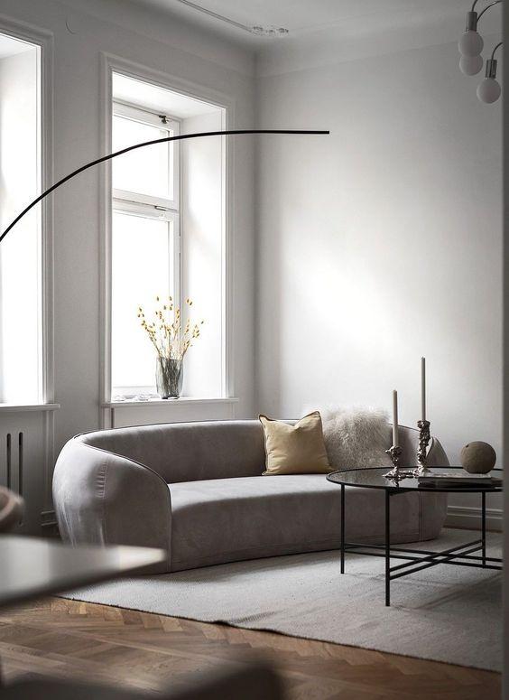 un soggiorno minimalista neutro con un divano curvo, una lampada a sospensione, un tavolino da caffè, cuscini e fiori in un vaso