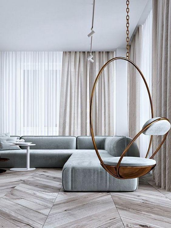 un soggiorno minimalista neutro con tende bianco sporco, un divano componibile grigio, una sedia sospesa in rame e un tavolino laconico