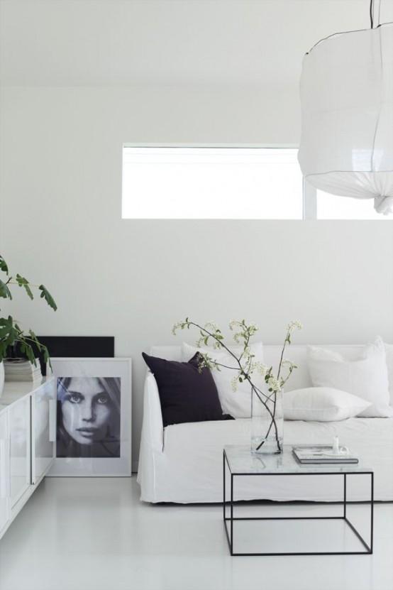 un soggiorno minimalista bianco puro con una piccola finestra, una lampada di carta e tocchi di nero per più drammaticità