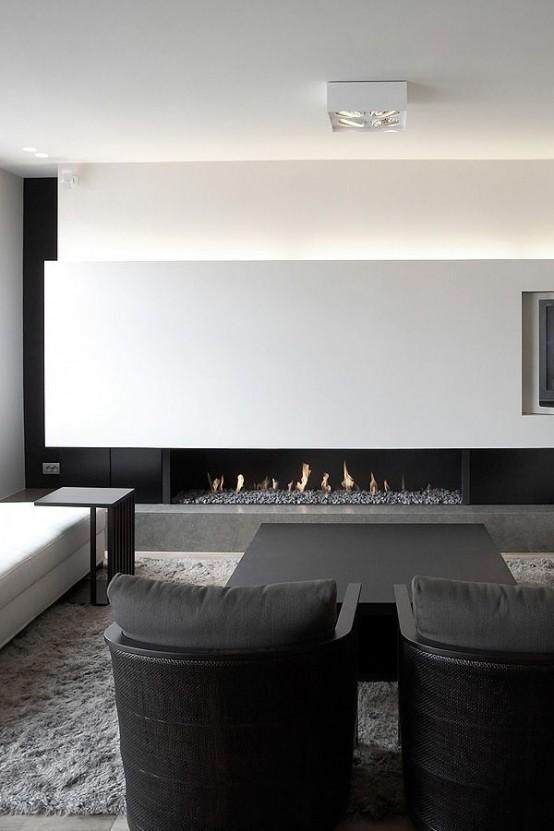 un soggiorno minimal in bianco e nero super elegante con una parete illuminata, un caminetto, comodi mobili in bianco e nero
