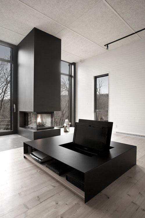 un soggiorno minimal con grandi finestre per la vista e la luce naturale, un focolare nero e un tavolino nero con una TV nascosta
