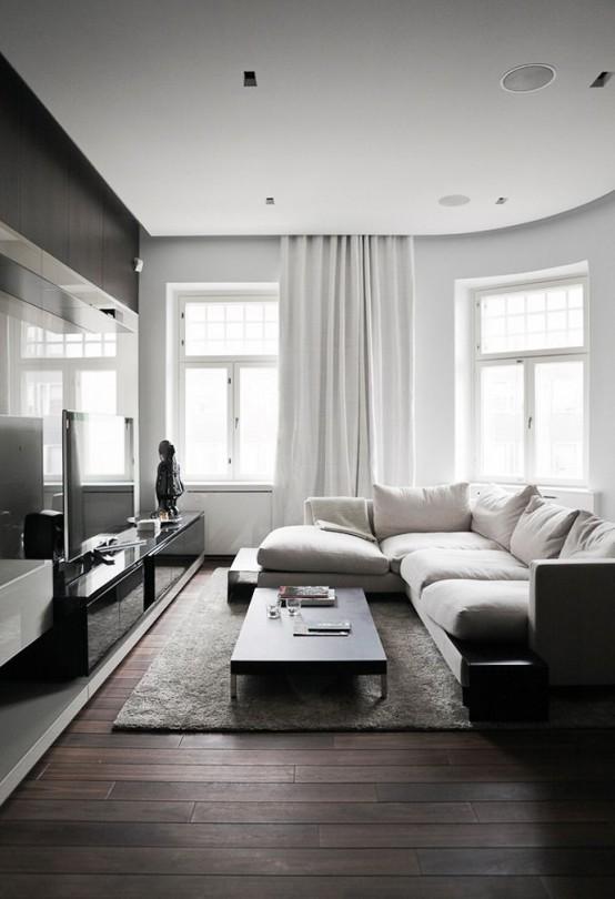 un soggiorno minimal monocromatico con mobili macchiati di scuro e un pavimento, pareti bianche, tende e un divano