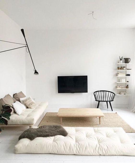 un soggiorno minimal neutro con cuscini bianco sporco, mobili in legno, una TV a parete e una lampada da parete