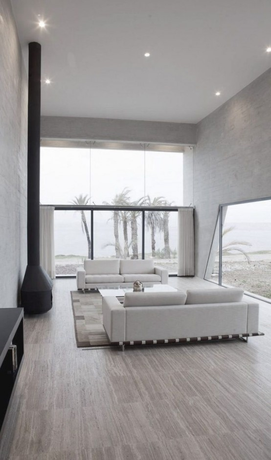 un soggiorno neutro minimalista con finestre di grandi dimensioni per riempire lo spazio di luce, un focolare e due divani bianchi
