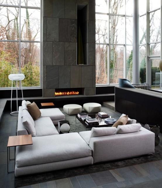 un soggiorno minimal con un grande divano componibile bianco, una parete del camino rivestita in pietra, soffitti a doppia altezza, una fossa di conversazione