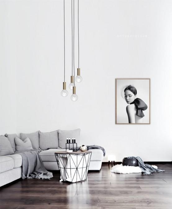 un soggiorno minimalista con un divano grigio, un'opera d'arte, un tavolo geometrico e lampade a sospensione