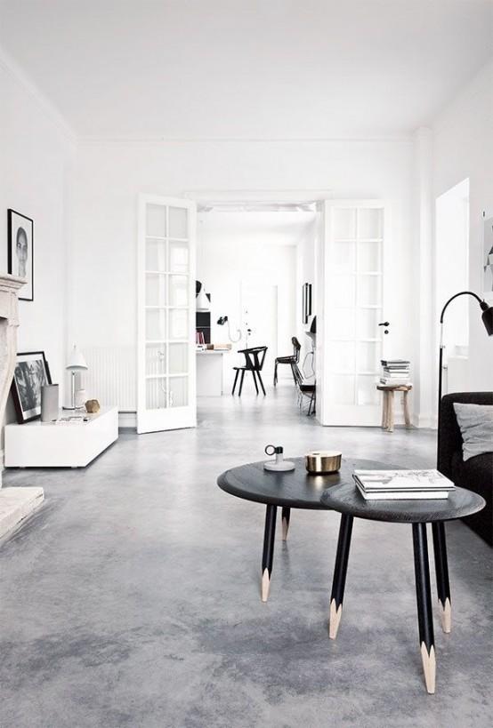 un minimal incontra un soggiorno nordico con un divano nero e tavolini da caffè, mobili bianchi e in legno e un caminetto
