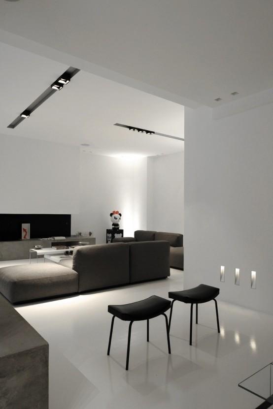 un soggiorno minimal bianco con una console di cemento, sgabelli neri e divani scuri