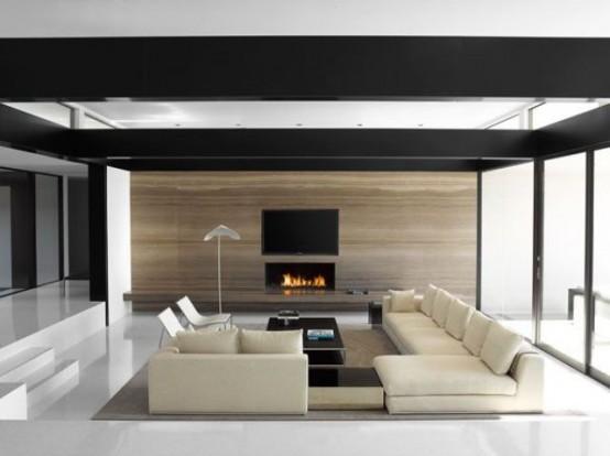 un soggiorno minimal con una buca per la conversazione, mobili contemporanei, un camino e un soffitto con cornice scura