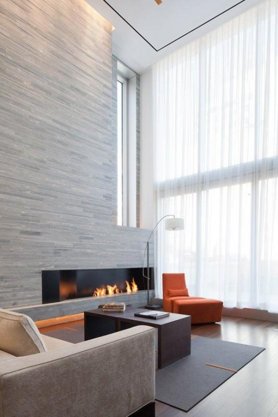 un soggiorno minimal a doppia altezza con una parete del camino rivestita in legno, mobili contemporanei e una grande finestra per una luce più naturale