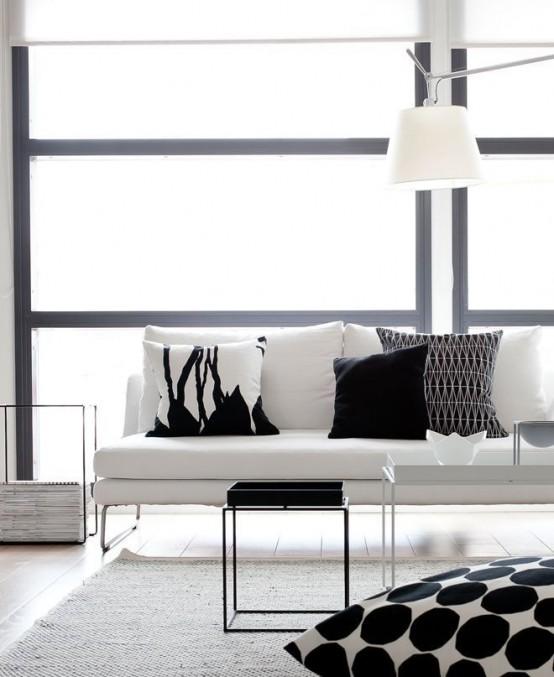 un soggiorno minimal in bianco e nero con un elegante divano bianco, cuscini stampati in bianco e nero e tavolini da caffè