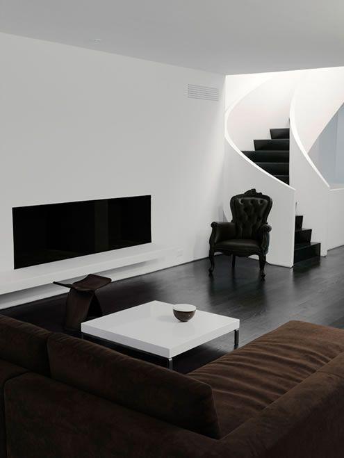 un soggiorno minimalista in bianco e nero con mobili eleganti e un divano componibile marrone scuro
