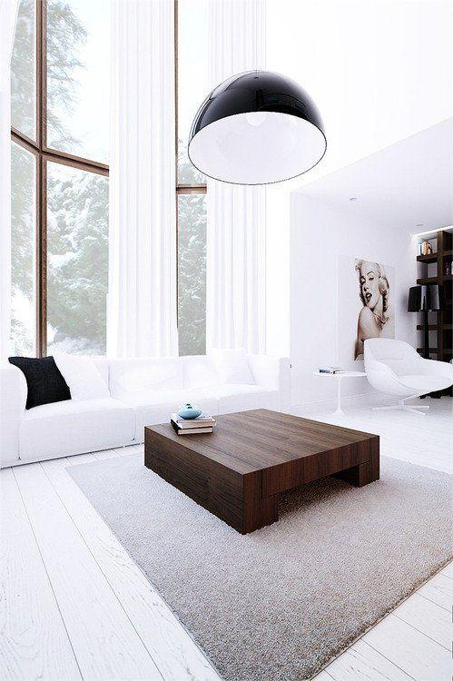 un soggiorno minimal bianco con finestre a doppia altezza, un divano bianco, un tavolino da caffè macchiato di scuro e una lampada a sospensione