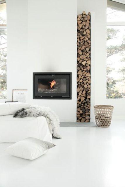 un soggiorno minimal tutto bianco con camino e spazio per la legna da ardere, un divano bianco e ampie finestre per più luce