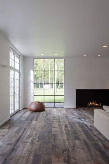 un soggiorno minimal con camino, divano bianco e ampie finestre che offrono molta luce naturale