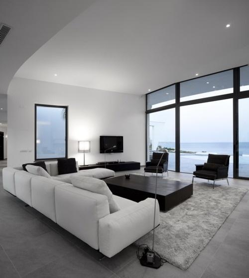 un elegante soggiorno minimalista bianco e nero con vista, mobili chic e un tappeto peloso sul pavimento