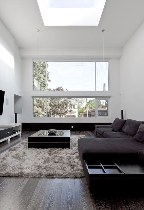 un soggiorno minimal chic e accogliente con mobili scuri, un soffice tappeto, una TV e una grande finestra più un lucernario