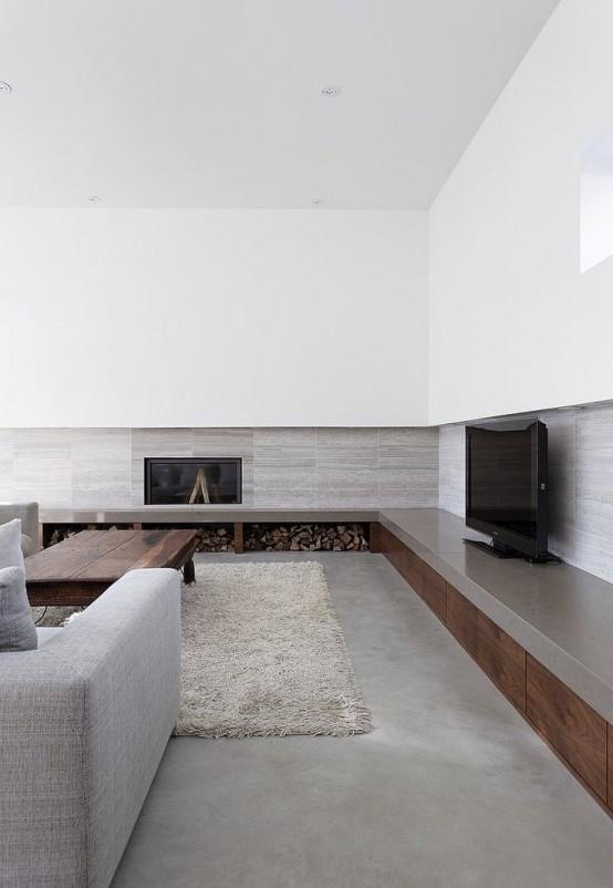 un elegante soggiorno minimal grigio e bianco con camino, legnaia, mobili grigi e un soffice tappeto