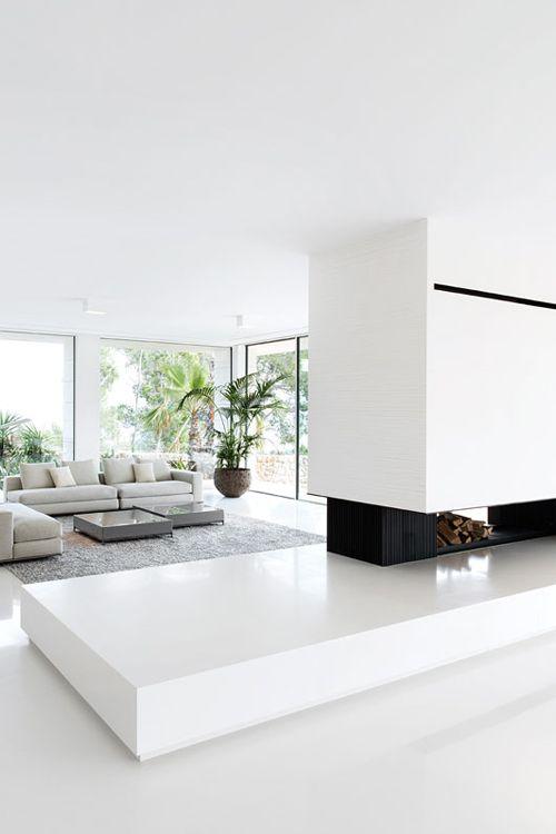 un soggiorno minimal e luminoso con camino e legnaia, divano componibile grigio e finestre panoramiche