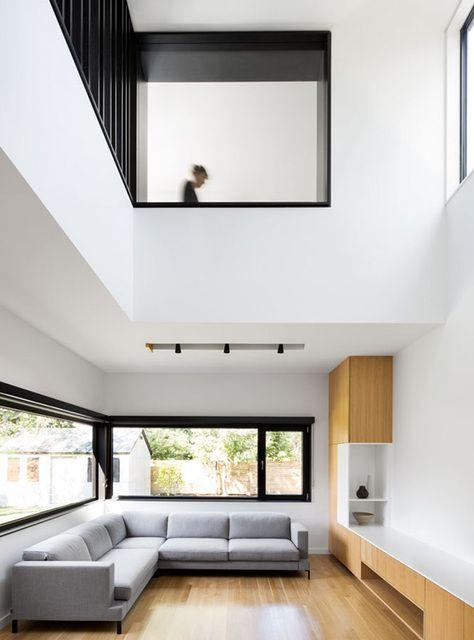 un soggiorno minimalista a doppia altezza con un divano componibile grigio, mobili in legno neutro, finestre per inondare lo spazio di luce