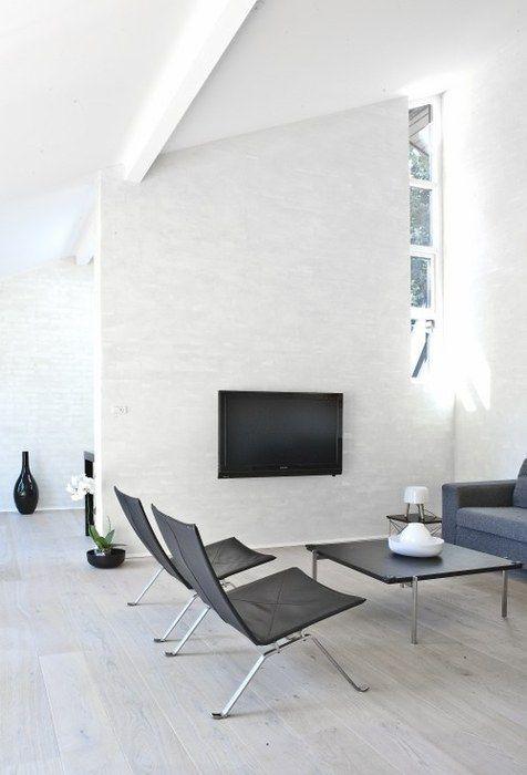 un soggiorno minimalista bianco con TV, finestre, mobili neri e grigi che sembra comodo e accogliente