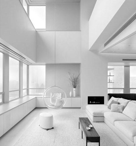 un soggiorno minimal bianco puro con camino incorporato, finestre, mobili bianchi e neri