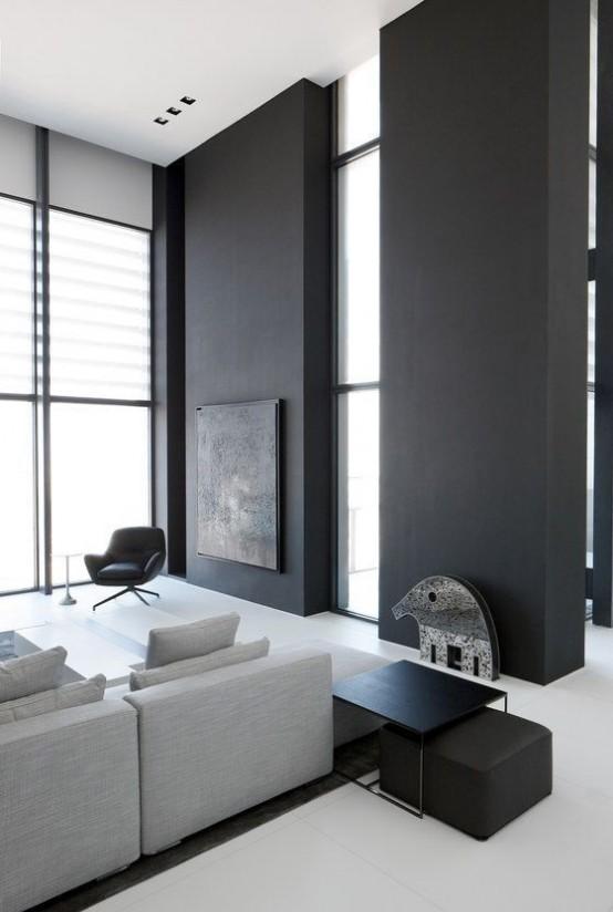 un soggiorno minimal con pareti nere, un divano componibile grigio, mobili neri e molta luce naturale