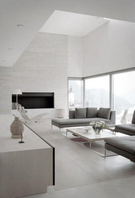 un soggiorno minimal neutro con camino, mobili grigi e una splendida vista dalle finestre