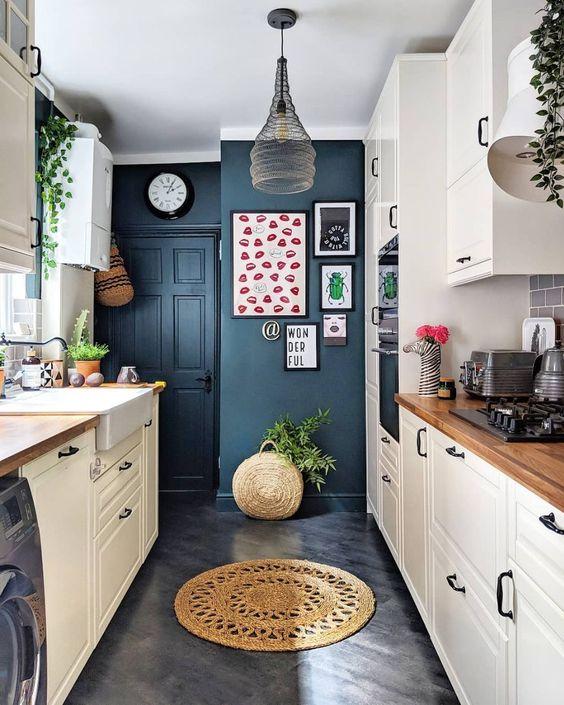 una piccola cucina stretta e lunga contemporanea con pareti blu scuro, armadi bianchi con ripiani in legno e una lampada a sospensione accattivante