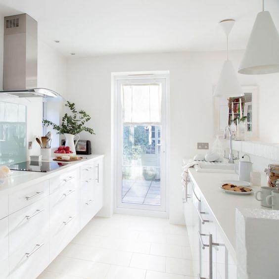una cucina stretta e lunga moderna cambusa bianca con armadi bianchi, tocchi in metallo e vetro e un accesso alla terrazza con molta luce